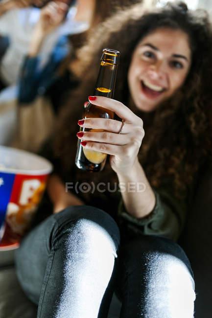 Ritratto di giovane donna sorridente che tiene in mano una bottiglia di birra — Foto stock