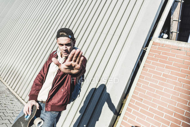 Portrait of aggressive young man with skateboard gesturing — Stock Photo