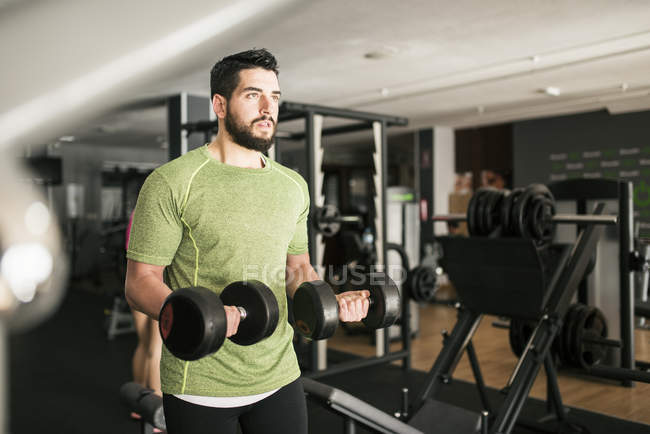 Sporty caucasian man training biceps in gym — Stock Photo
