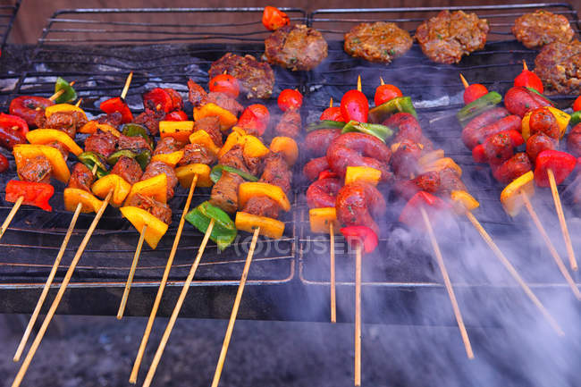 Meat and vegetables barbecued on wooden sticks — Stock Photo