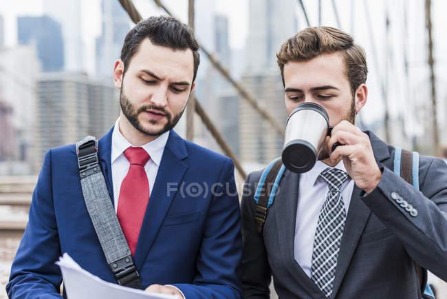 États-Unis, New York, Brooklyn Bridge, deux hommes d'affaires marchant en ville avec des papiers et une tasse de café — Photo de stock