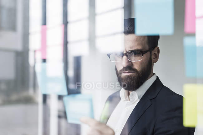 Portrait of young businessman sticking notes — Stock Photo