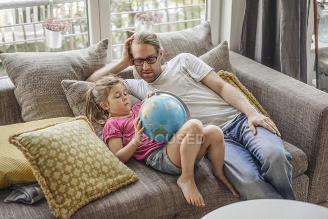 Vater und Tochter liegen mit Globus auf Sofa — Stockfoto