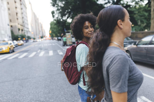 USA, New York City, two friends crossing the street — Stock Photo