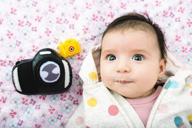 Portrait of baby girl lying on bed with two toy cameras — Stock Photo