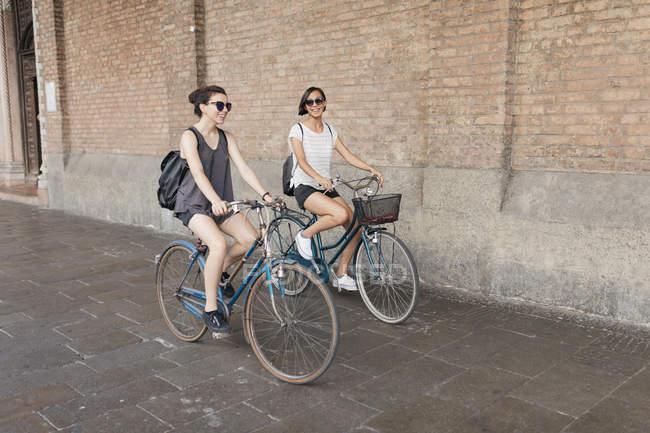 Dos mujeres jóvenes que andan en bicicleta en la ciudad de - foto de stock