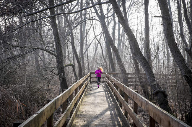 Frau läuft auf Holzbrücke durch Wald — Stockfoto
