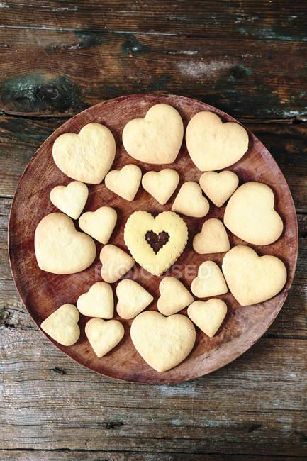 Galletas caseras en forma de corazón en la placa de madera - foto de stock