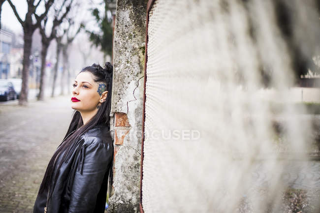 Daydreaming young woman leaning against wall — Stock Photo