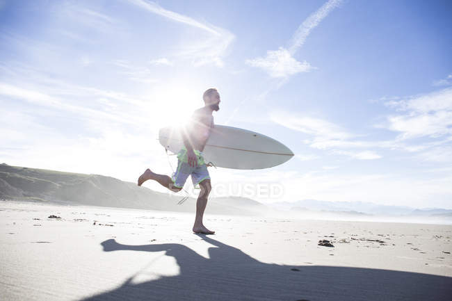 Man with surfboard running on sandy beach in backlit — Stock Photo