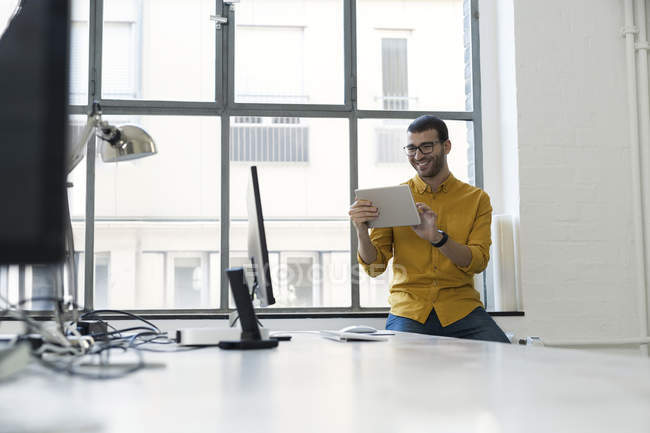 Young businessman using digital tablet in office — Stock Photo
