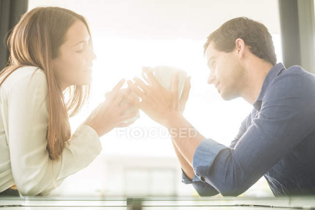 Пара холдингу чашки у підсвічуванням — стокове фото