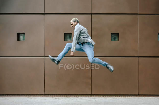 Businessman jumping for joy in front of modern building — Stock Photo