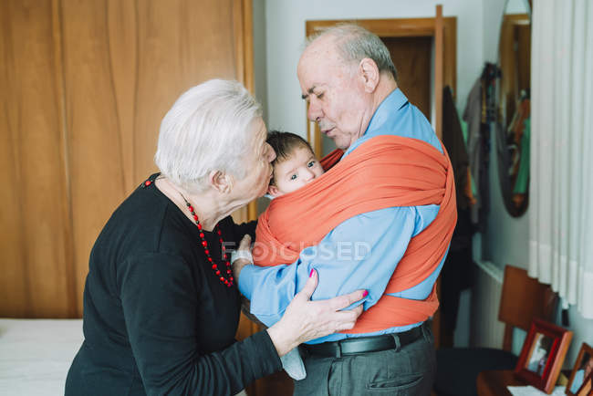 Great-grandparents with baby at home — Stock Photo