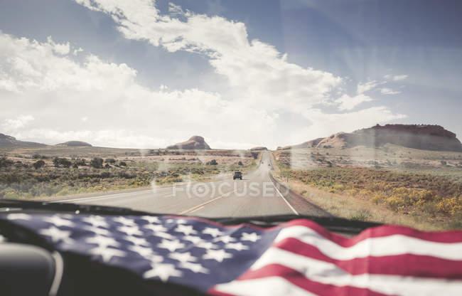 Внутренний вид автомобиля с флагом США и дороги на заднем плане в дневное время — стоковое фото