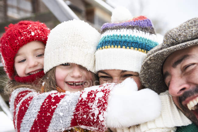 Portrait of happy family hugging in winter — Stock Photo