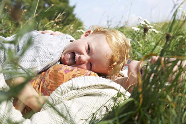 Felice madre e figlio sdraiato nel prato — Foto stock