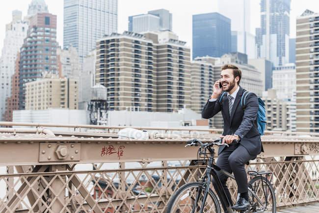 США, Нью-Йорк, Бруклинский мост, Молодой бизнесмен в костюме ездит на велосипеде и разговаривает по телефону — стоковое фото