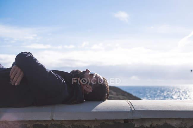 Людина розслабляючий на стіну з моря на тлі — стокове фото
