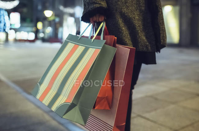 Woman with shopping bags on pavement, partial view — Stock Photo