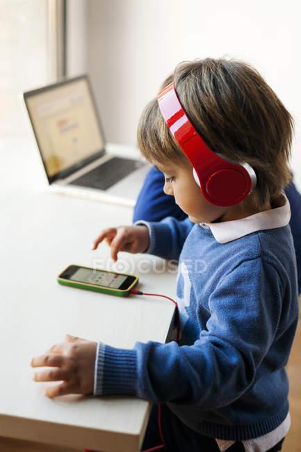 Retrato lateral de menino com fones de ouvido usando telefone celular — Fotografia de Stock