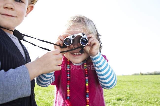 Мальчик и девочка с биноклем на лугу — стоковое фото