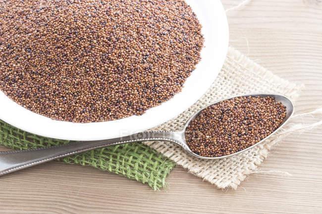 Semi di quinoa in ciotola e il cucchiaio su superficie di legno — Foto stock