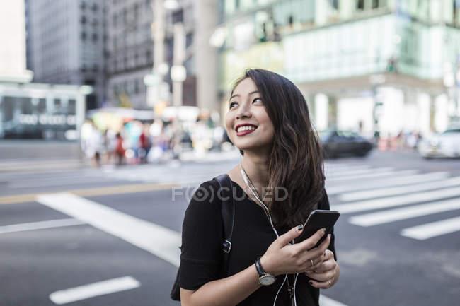 Retrato de mujer asiática joven sosteniendo teléfono inteligente en la calle - foto de stock