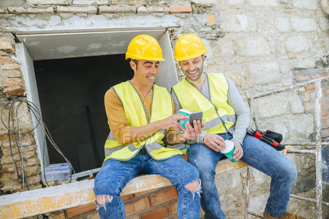 Two construction workers looking at a mobile phone at break time. — Stock Photo