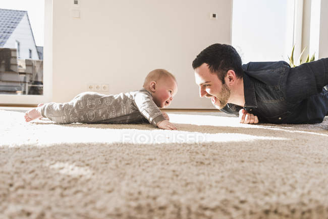 Fils de père et bébé jouant à ramper sur le tapis à la maison — Photo de stock