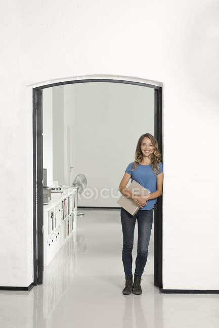 Casual businesswoman leaning against door frame and holding folder in office — Stock Photo