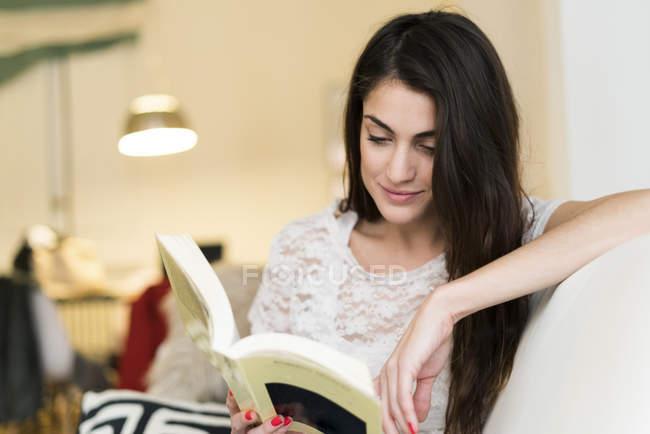 Жінка сидить на дивані і читав книгу — стокове фото