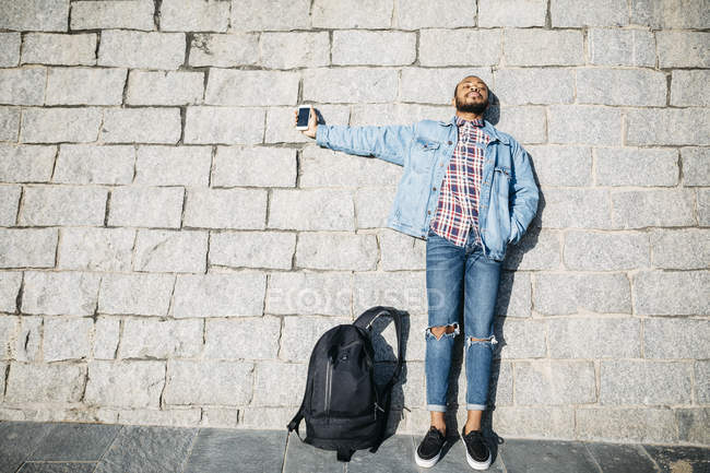 Young traveler using mobile in the wall. — Stock Photo