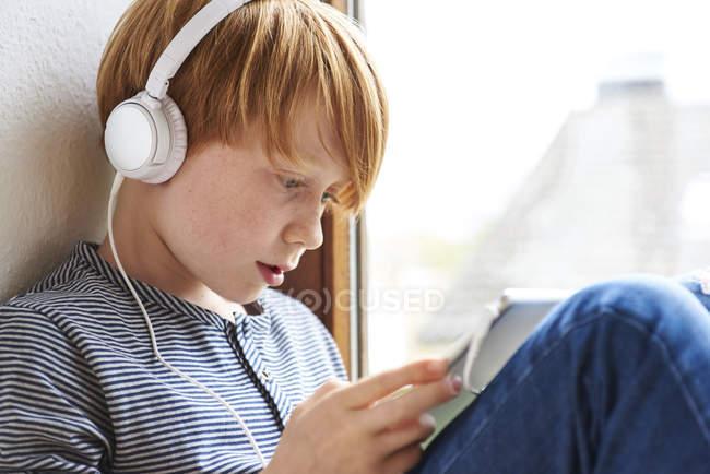 Niño pelirrojo en auriculares usando tableta digital - foto de stock