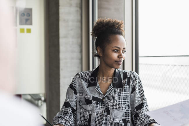 Woman sitting in office — Stock Photo