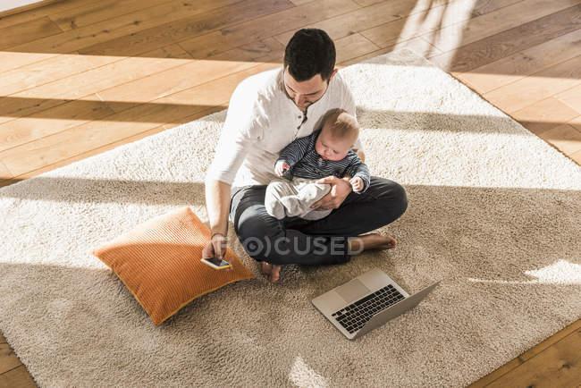 Батько турецьки з дитину сина на колінах, використовуючи ноутбук і смартфонів — стокове фото