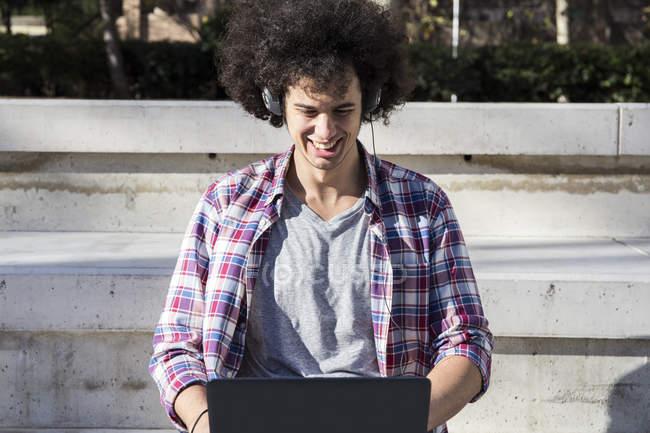 Jovem sorridente usando laptop e fones de ouvido na cidade — Fotografia de Stock
