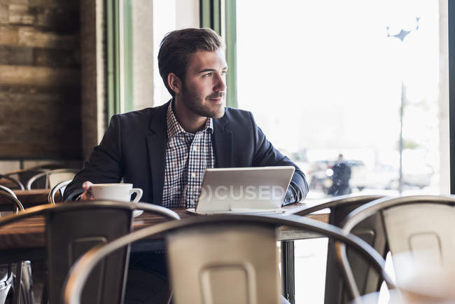 Thoughtful businessman using tablet in cafe — Stock Photo