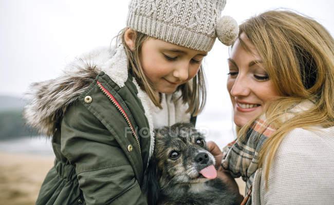 Espagne, Asturies, Portrait de fille heureuse avec chapeau et femme souriante avec écharpe caressant leur chien à la plage — Photo de stock