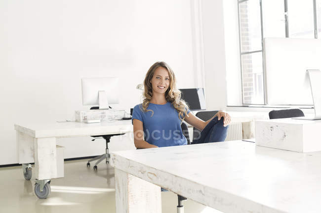Casual businesswoman sitting in office and looking at camera — Stock Photo