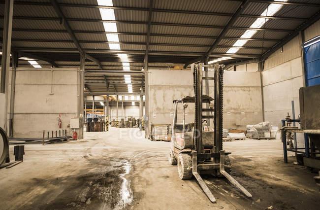 Vecchio carrello elevatore nel corridoio disordinato della fabbrica — Foto stock