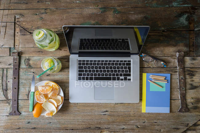 Top view of laptop with sliced orange and detox water — Stock Photo