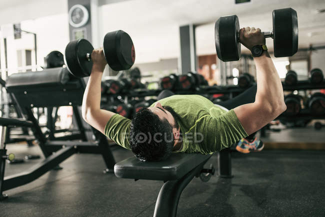 Man training pectoral muscle lifting weights in gym — Stock Photo