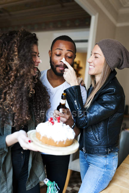 Portrait of young woman putting cream on nose of man — Stock Photo