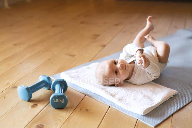 Ребенок лежит на коврике рядом с гантелями дома — стоковое фото