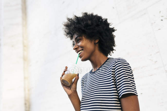 Young attractive african american woman drinking beverage from cup by straw — Stock Photo