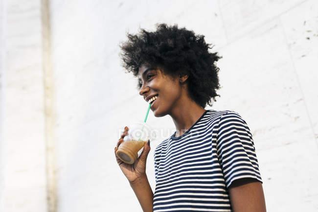Jeune femme afro-américaine attrayante buvant boissons à coupe de paille — Photo de stock