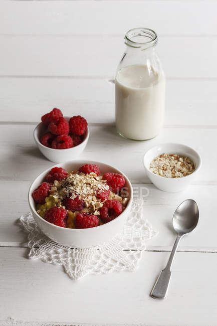 Closeup view of oat flakes with raspberries and milk — Stock Photo