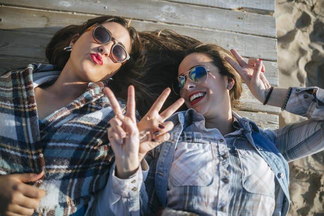 Портрет двух молодых женщин, лежа на деревянной палубе и делать смешные лица — стоковое фото