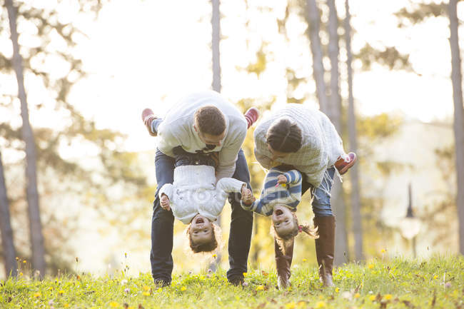 Playful family with two girls on meadow — Stock Photo